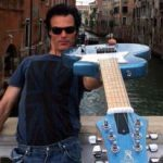 Yup! That's Venice behind me and my Voyage-Air guitar—a full-size electric guitar that folds in half for travel.